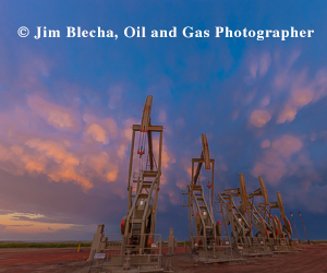 Ad - Jim Blecha, oil and gas photographer. Five pumpbacks with sunset sky.