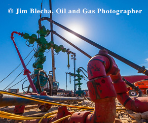 Ad - Jim Blecha, oil and gas photographer. Green frac tree with red pipe in foreground.