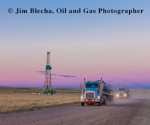 Ad - Jim Blecha, oil and gas photographer. Two semi trucks driving on dirt road past drilling rig at sunset.