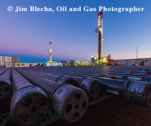 Ad - Jim Blecha, oil and gas photographer. Two rigs with pipes in foreground.